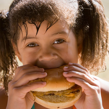 photo of girl eating hamburger