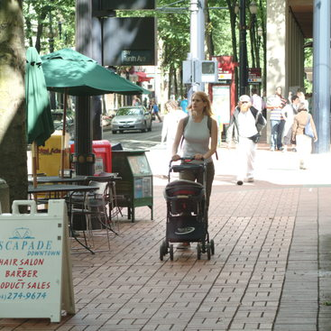 photo of a mom with stroller walking in a downtown center