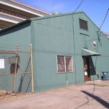 industrial building covered with green corrugated aluminum siding