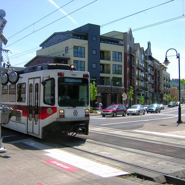 a photo of a MAX light rail train eclipsing a building in the background