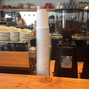 Stack of paper coffee cups at a cafe
