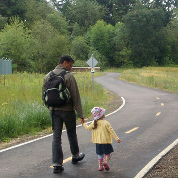 father and young daughter walk together on Fanno Creek Trail