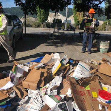 two workers in hard hats and safety vests standing next to a pile of cardboard and paper being sorted for recycling