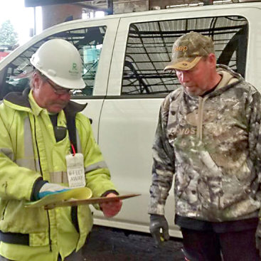 transfer station worker checking a clipboard while helping a customer