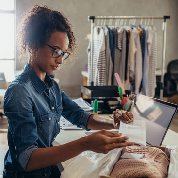woman prepares to ship an order from a clothing boutique