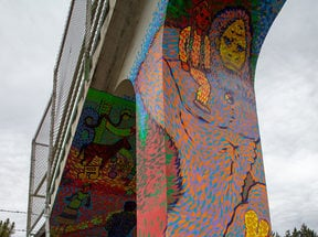 a colorful big foot painted on the column of a pedestrian bridge