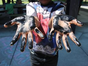 a child holds out his hands covered in paint