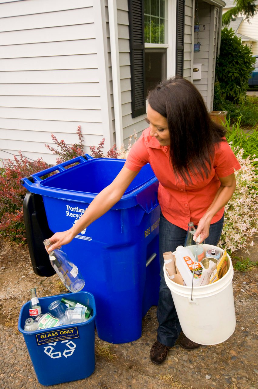 photo of woman sorting glass into a separate bin