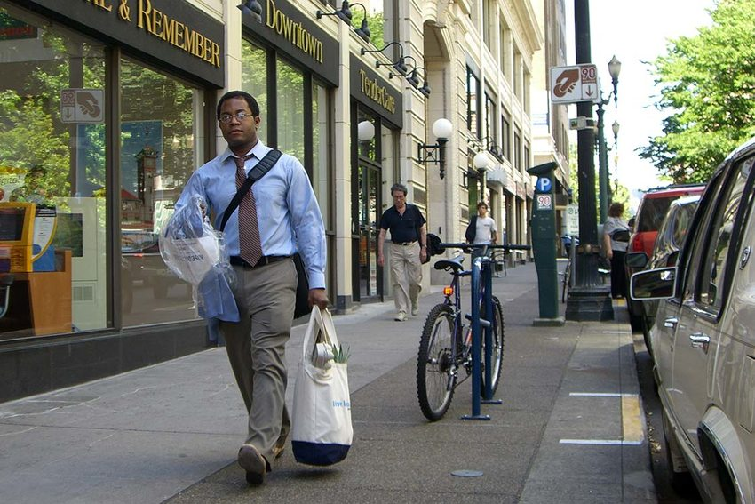 photo of man walking with dry cleaning