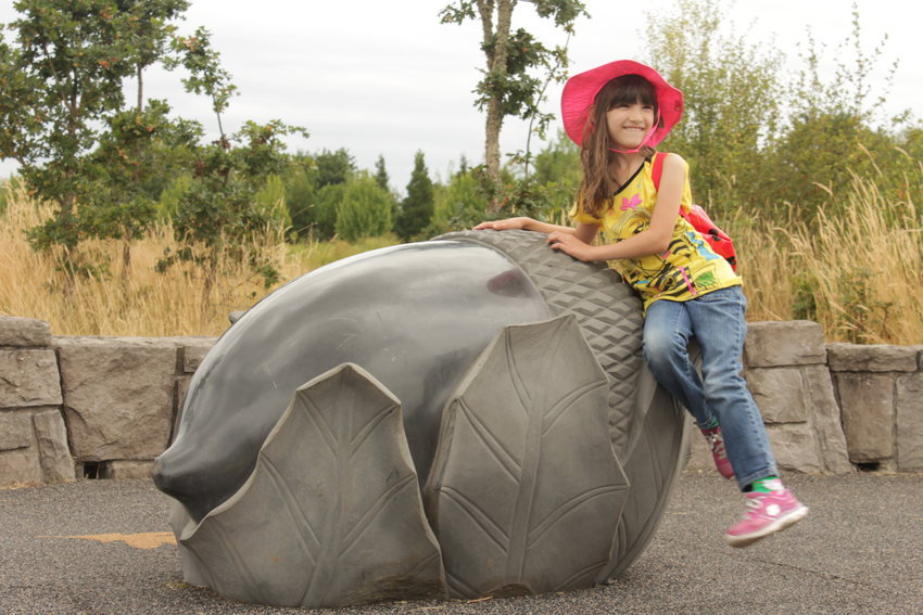 Little girl at acorn statue at Graham Oaks Nature Park