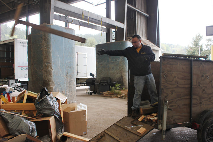 Lalo Gonzalez of Schopp's Maintenance unloads hauled away items, tossing boards and more into the heap.