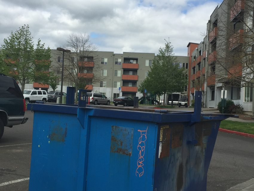 dumpster in parking lot of apartment complex