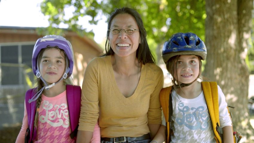 smiling mother with two young daughters wearing bicycle helmets