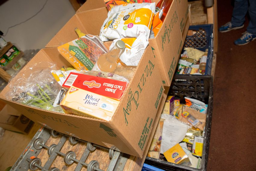food donations packed into cardboard boxes on a conveyor belt