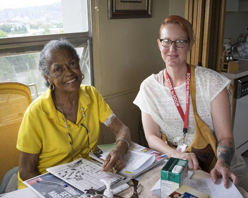 elderly resident and outreach volunteer solve a crossword puzzle