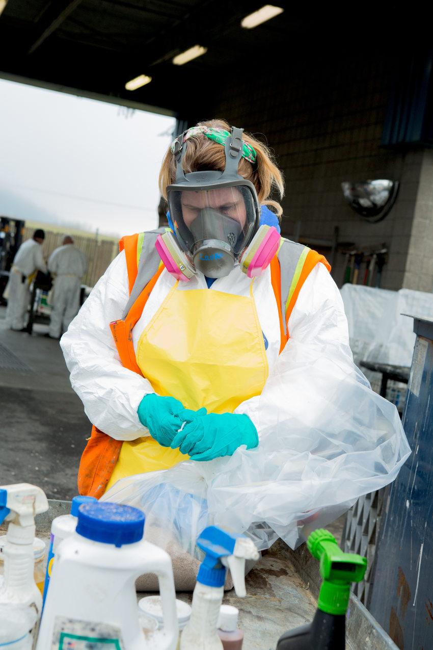 Metro employee wearing mask and sorting hazardous waste recycling.