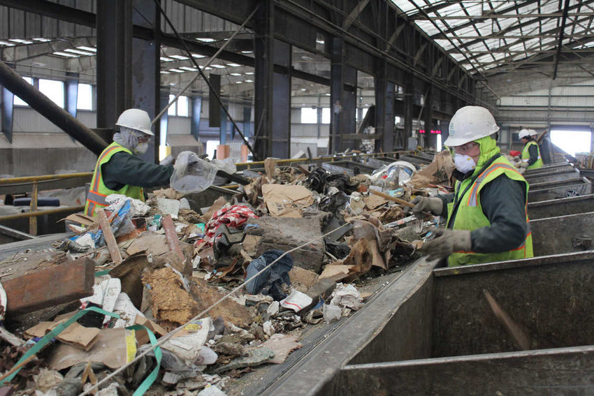 workers sort trash on the line at the transfer station.