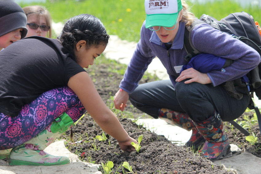 children and an instructor tend to seedlings in a garden at Sauvie Island Center