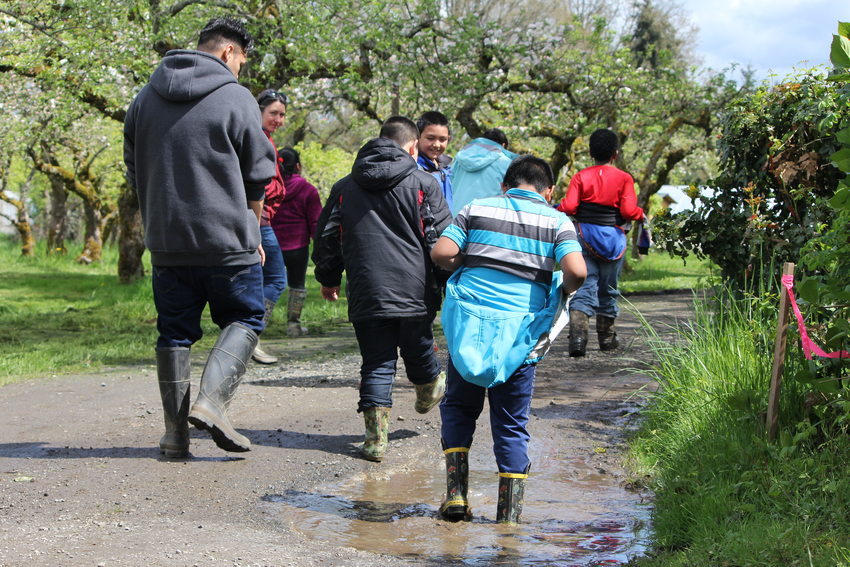 children wearing rubber boots walk along a puddle-filled dirt road at Sauvie Island Center