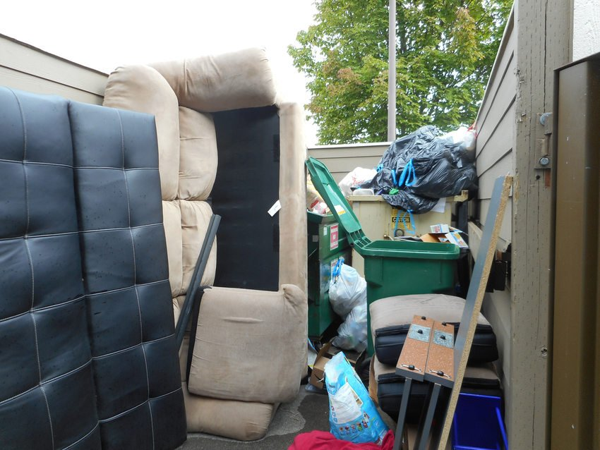 couch and other furniture in recycling area alongside recycling bins and dumpster