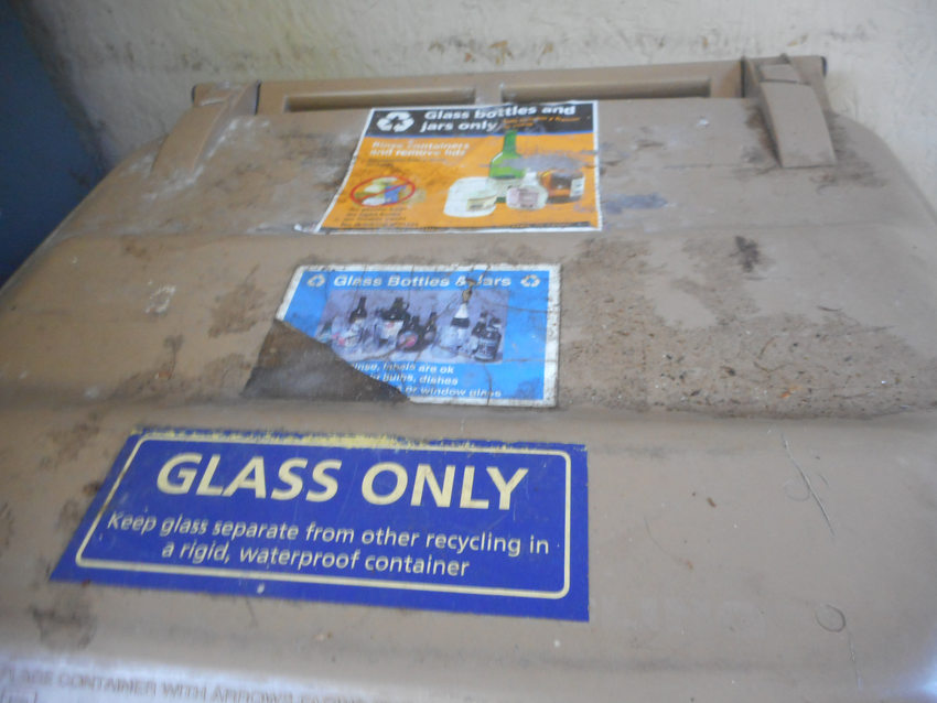 """lid of recycling bin with blue label reading """"glass only"""""""