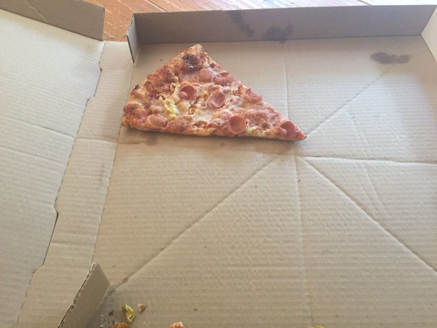 A lone slice of pizza in a pizza box