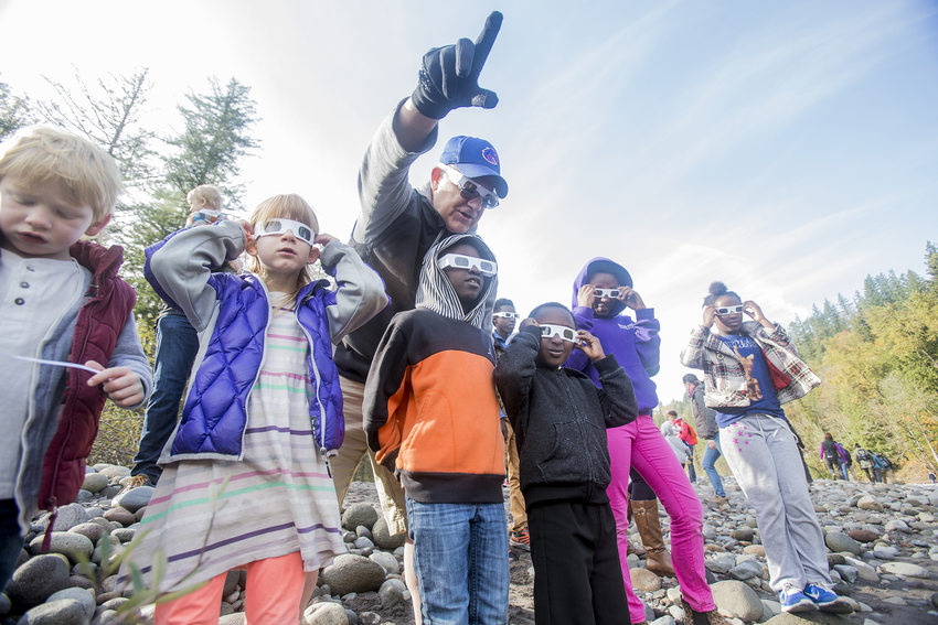 group of children wearing 3D glasses with man pointing to an object in the distance