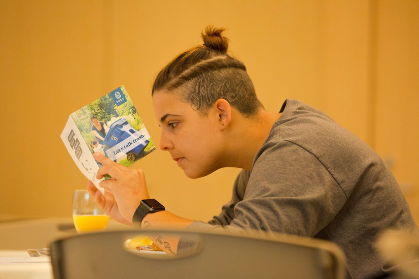 Participant Valerie Curbelo reading a booklet distributed by staff at the series kickoff
