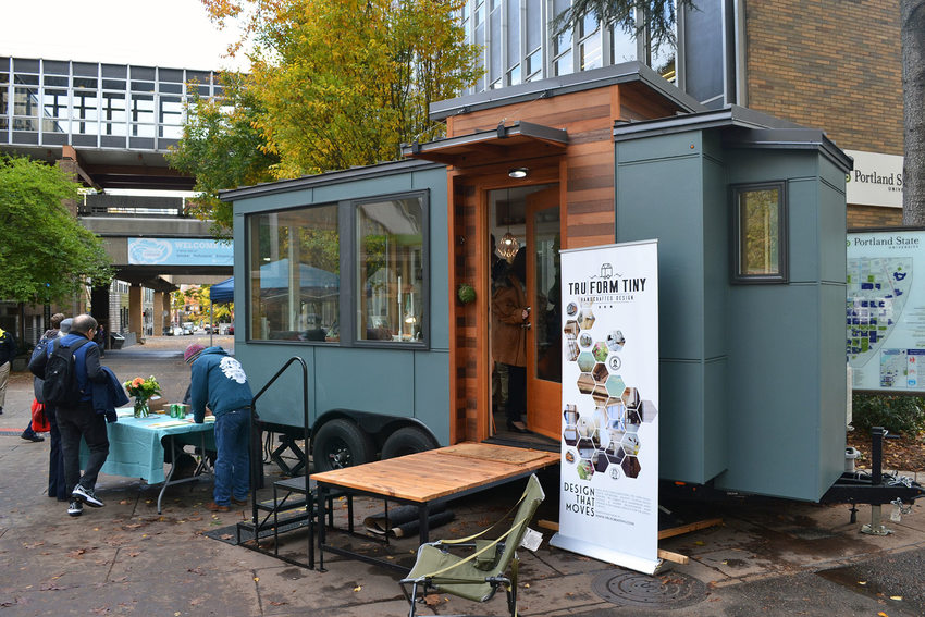 A blue tiny house on wheels on display at a conference at Portland State University