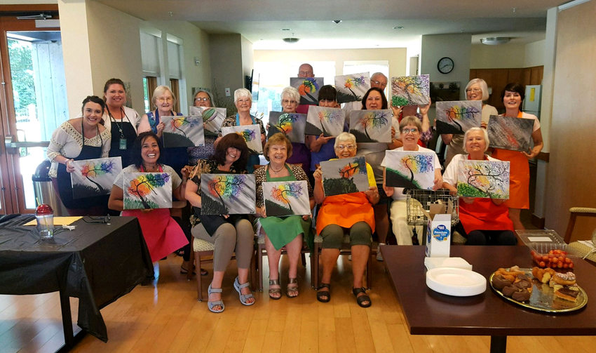 Creekside Woods senior citizens show off their paintings after an art class.