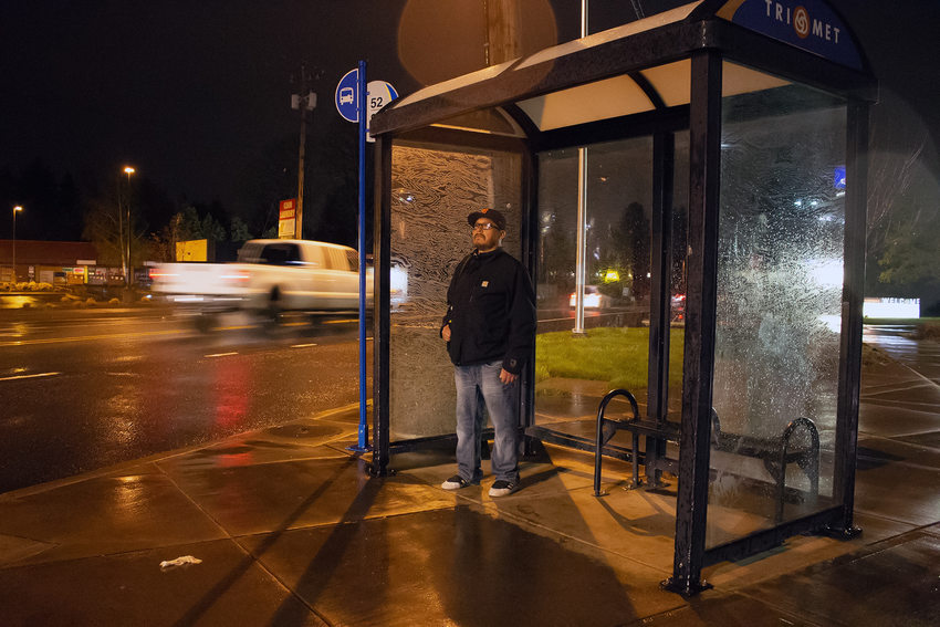 A man waiting for the bus at a bus stop at about 5:30 in the morning.