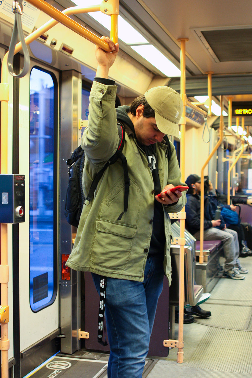 AJ Romero-Gemmell holds on to a handrail while standing in a MAX light rail train.