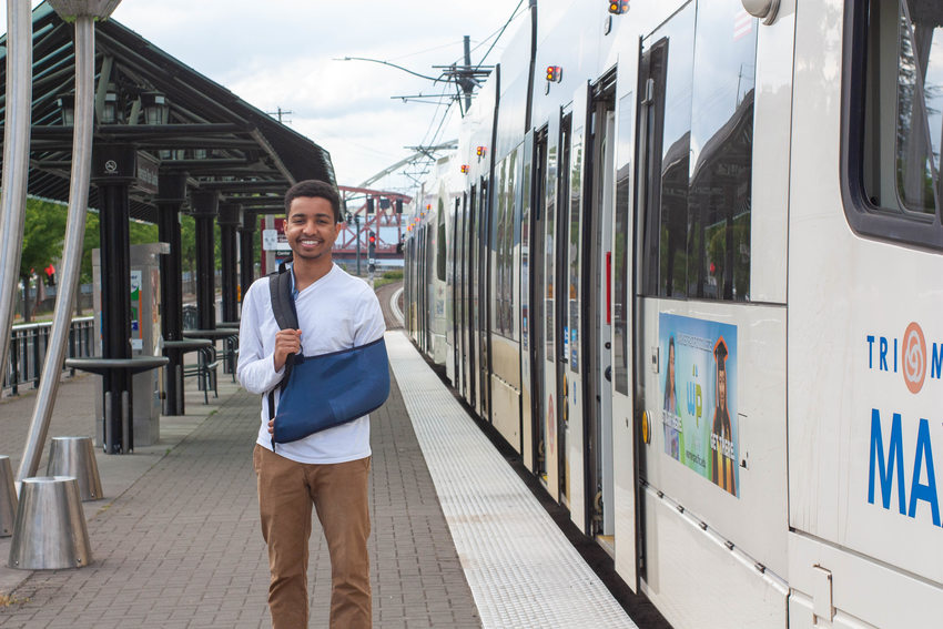 A portrait of 18-year-old Ibrahim Ibrahim standing on the platform of a MAX light rail station with the train in the background.