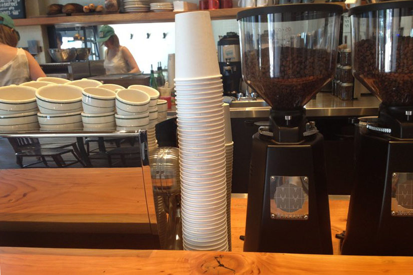 scene of a coffee shop with stacked paper coffee cups at the counter