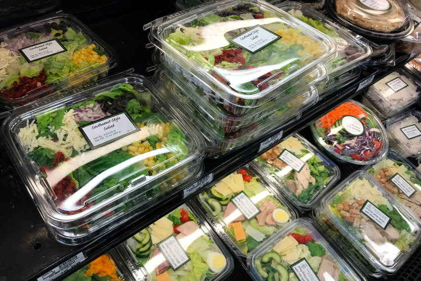 rows of deli salads in plastic clamshells in a grocery store