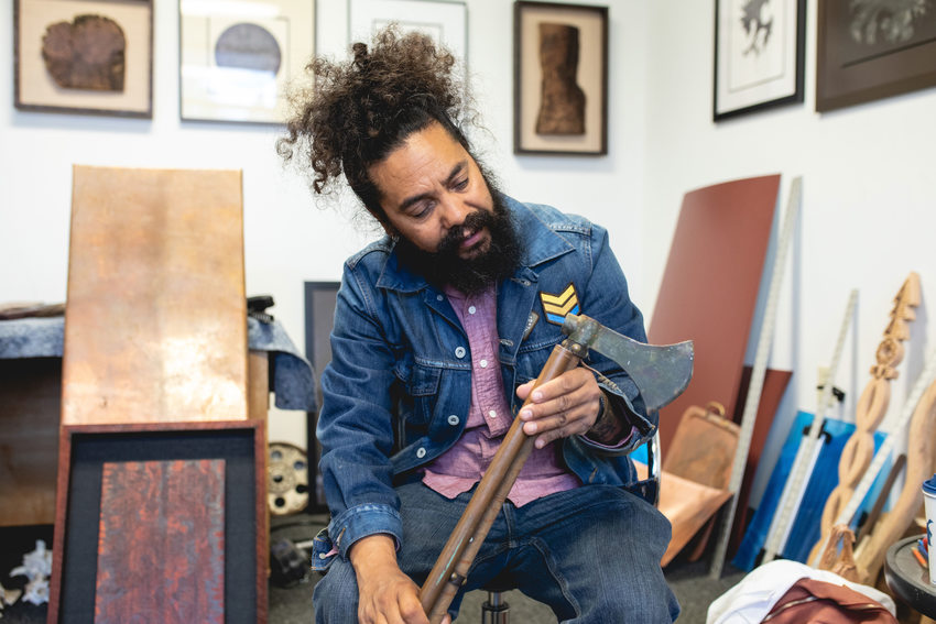 Artist in his studio looks an an antique ax he found in the trash.