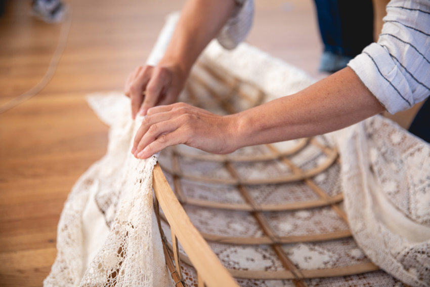 "Close-up of hands adding lace ""skin"" to a wooden boat frame."