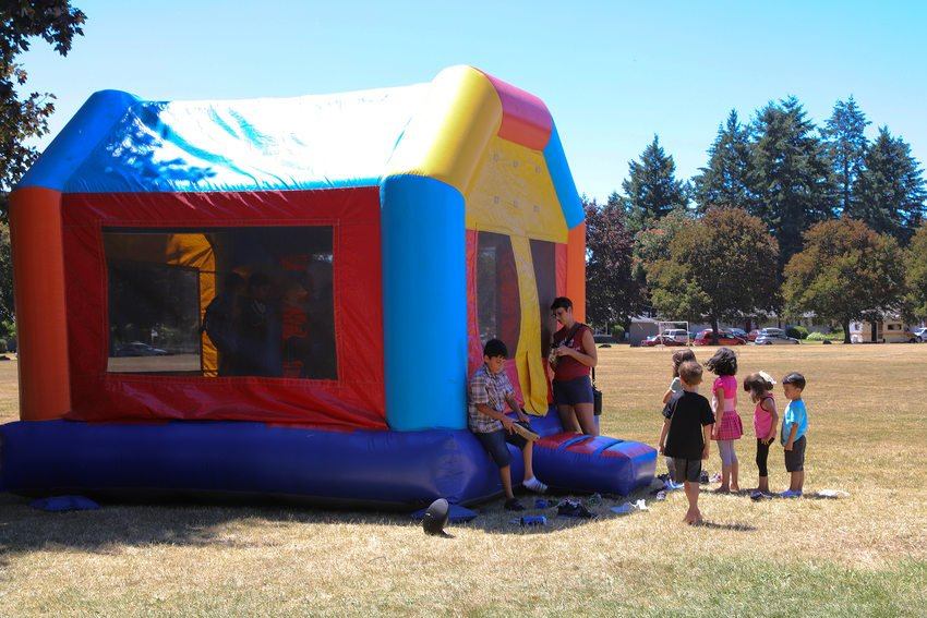 A colorful inflatable bounce house with neighborhood children waiting to enter.