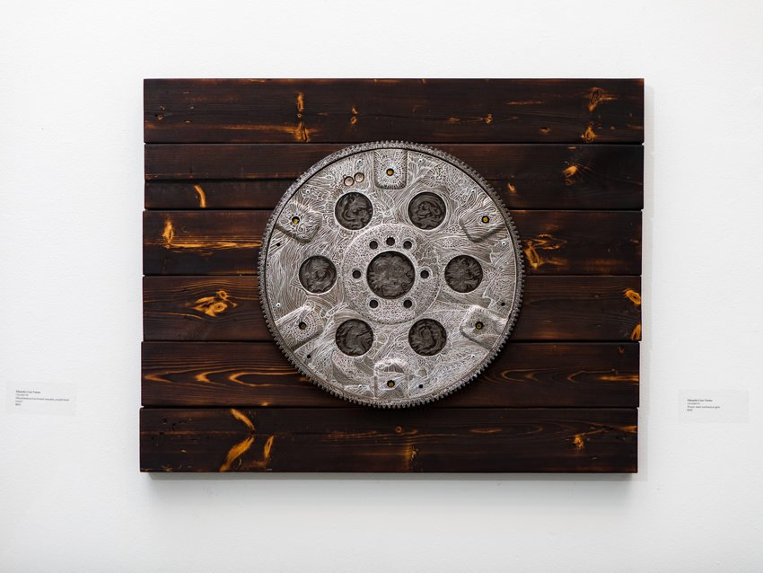 A round piece of metal, etched and mounted on wood