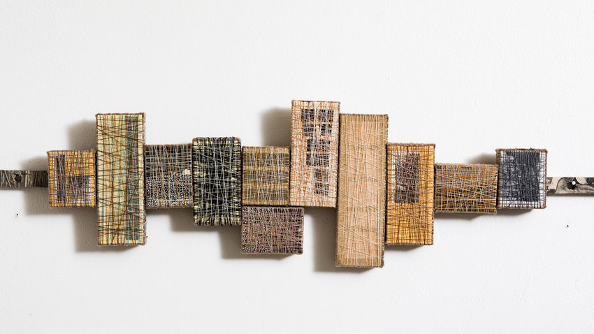 small blocks covered with patterns of thread, lined up and mounted on the wall