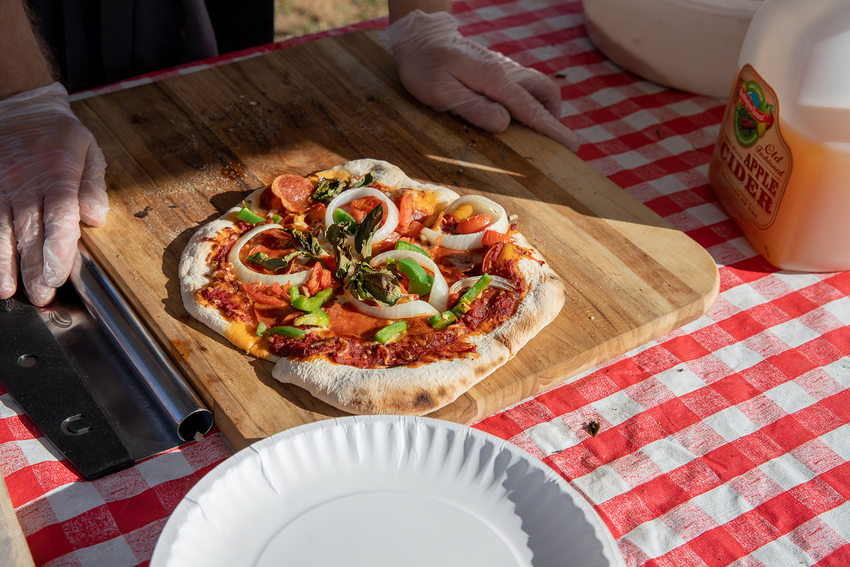 a yet-to-be-cooked pizza on a wooden chopping block that's on a table with a red and white checkered table cloth