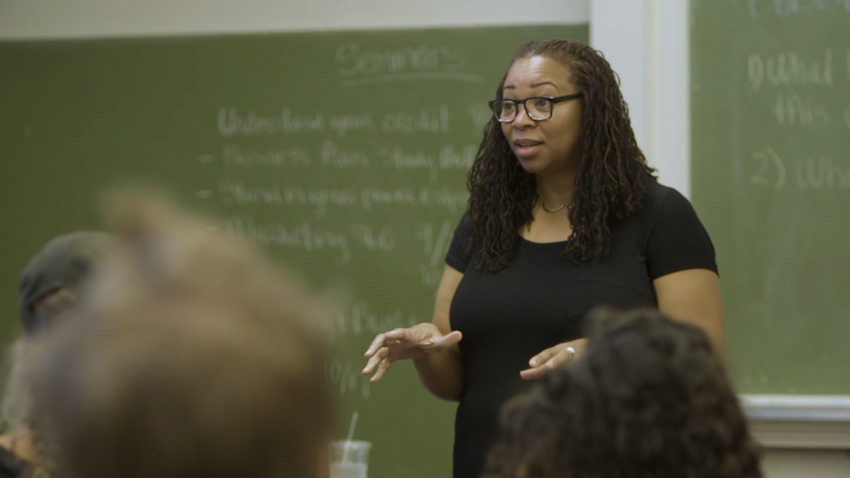 an instructor stands in front of her class with a green chalkboard behind her