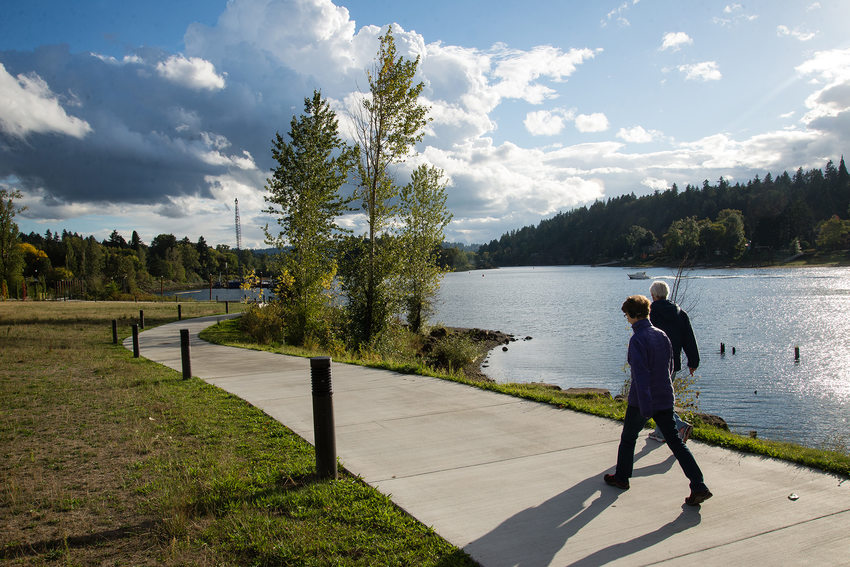 People walk along the river in Milwaukie Oregon
