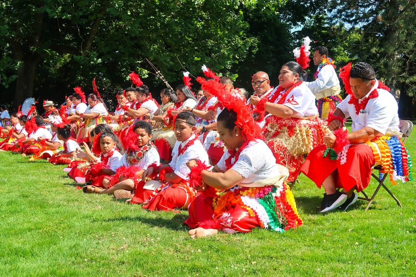 Tongan particants dressed in colorful attire seated on the grass and chairs.