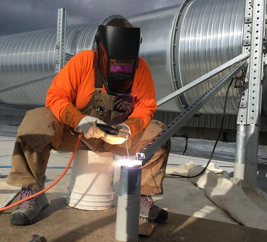 Female welder doing metal work