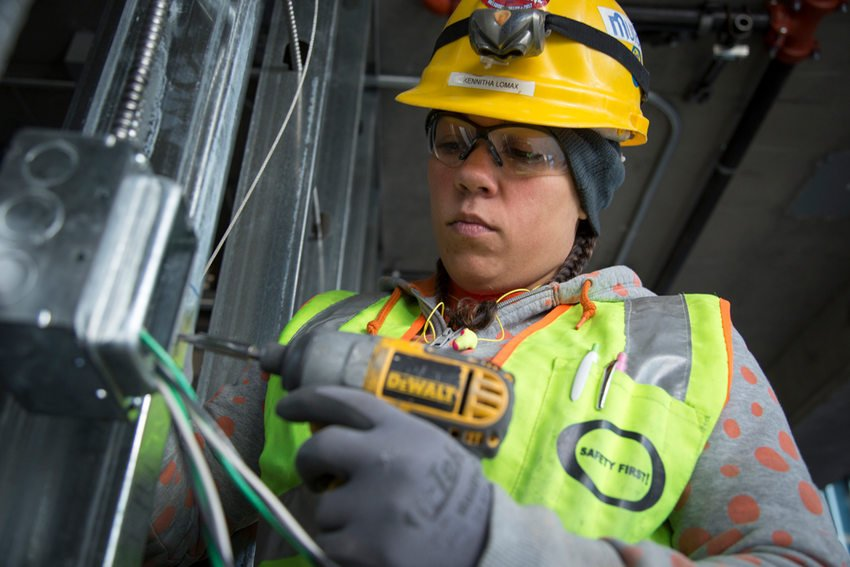Woman wearing hard hat drilling into building frame