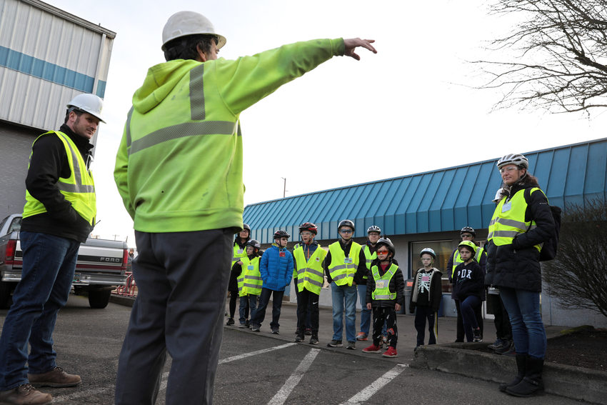 A group of kids in reflective vests listen to man in a hardhat