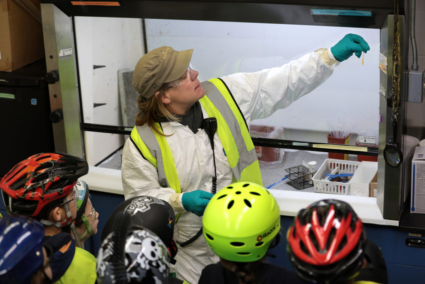 a woman holds up a liquid-filled test tube to a group of kids
