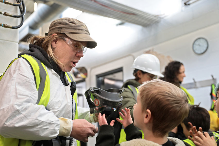 a woman in protective gear hands out gas masks to a group of kids