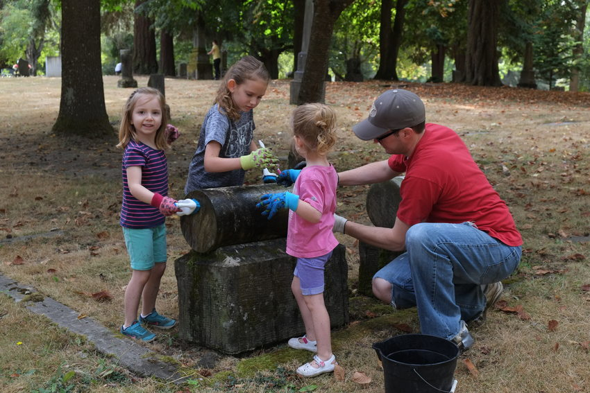 Young volunteers cleaning headstone at Lone Fir Cemetery
